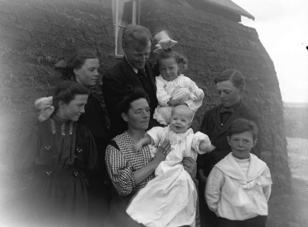 Ernest C. Stark family near their sod house southeast of present day Ollie, MT, 1909:  Gertrude and Gulnare (standing at left); Ernest holding Carol; Jay and Howard (standing at right); Ora holding baby Ernest B.