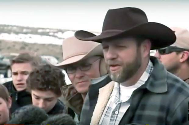 Ammon Bundy addresses the media while the late Lavoy Finicum stands in support during a Jan. 4, 2016 press conference they hosted a the Malheur Wildlife Refuge. Image taken from video