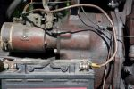 Battery terminals with old cables in focus and the engine with corrosion in the blurred background, outdoor cropped shot